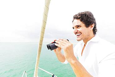 Hispanic man looking out from boat deck with binoculars