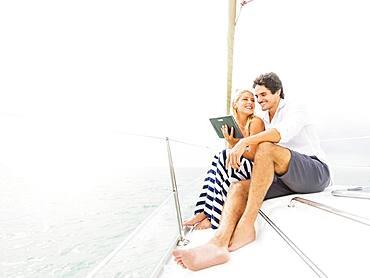 Couple using digital tablet boat deck