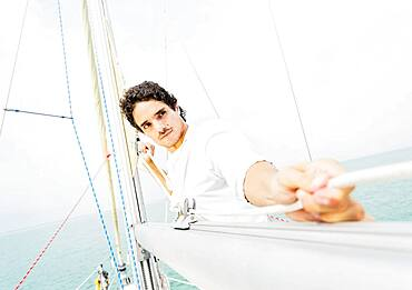 Hispanic man adjusting rigging on sailboat