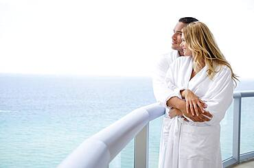 Couple hugging on balcony over ocean