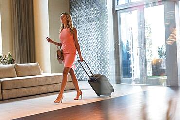 Woman rolling luggage in hotel lobby