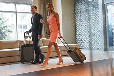Couple rolling luggage in hotel lobby