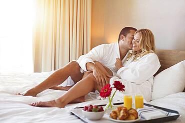Couple enjoying breakfast in bed in hotel room