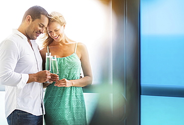 Couple drinking champagne at window