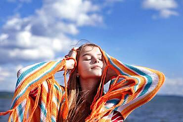 Caucasian teenage girl smiling with shawl