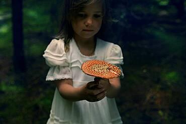 Caucasian girl holding mushroom in forest