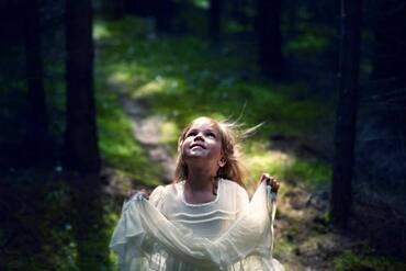 Caucasian girl playing in forest