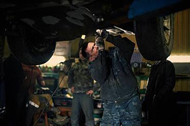 Caucasian mechanic fixing car