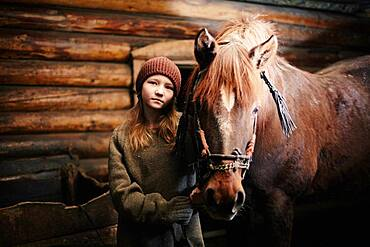 Caucasian teenage girl standing with horse in barn