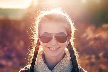 Caucasian teenage girl wearing sunglasses in field