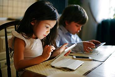 Caucasian brother and sister using digital tablets