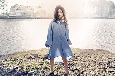 Caucasian girl standing at rural lake