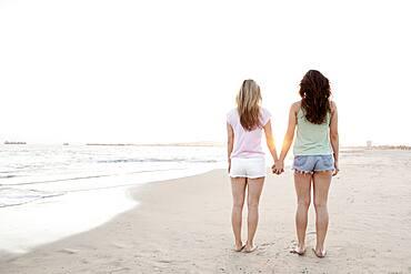 Women holding hands on beach