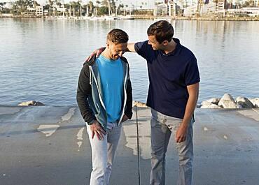 Caucasian man comforting friend at waterfront
