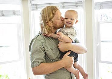 Caucasian father kissing son indoors
