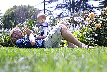 Caucasian father and son playing in grass