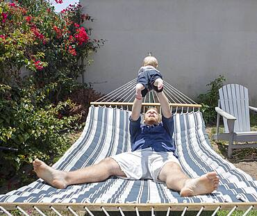 Caucasian father and son playing on hammock