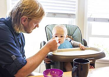 Caucasian father feeding son in high chair