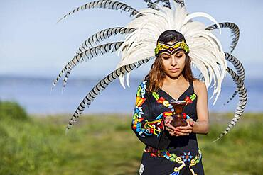 Native American woman in traditional headdress performing ceremony