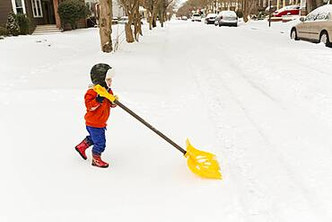 Caucasian boy shoveling snow
