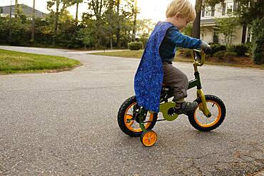 Caucasian boy riding bicycle with training wheels