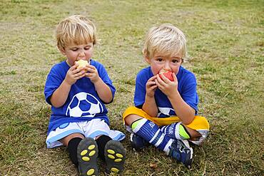 Caucasian soccer players eating apples