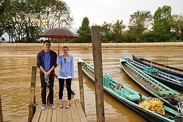 Couple standing under umbrella on wooden dock