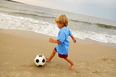 Caucasian boy playing with soccer ball on beach