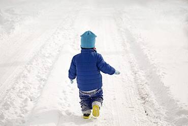 Caucasian boy walking in tire tracks in snow