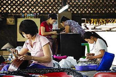 Asian artisans carving traditional designs in workshop