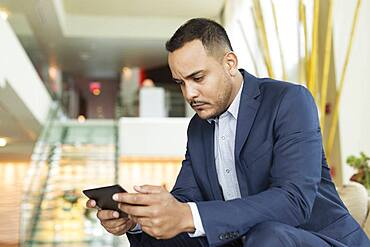 Hispanic businessman using digital tablet in hotel lobby