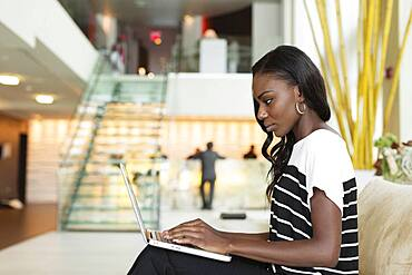 Businesswoman using laptop in hotel lobby