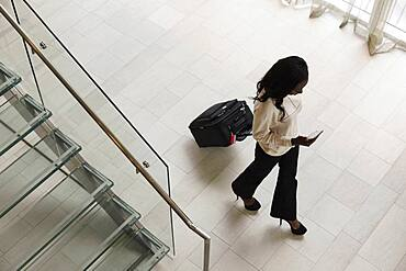 High angle view of businesswoman rolling luggage in hotel lobby