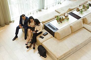 Business people using cell phones in hotel lobby