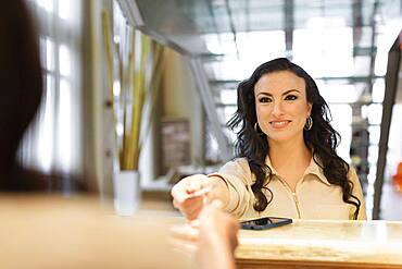 Businesswoman checking into hotel with concierge