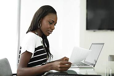 Businesswoman reading notes at office desk