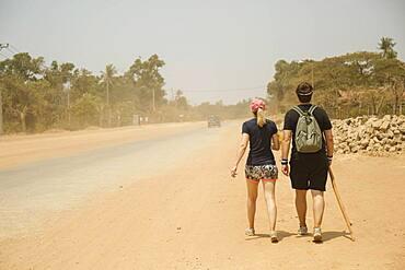 Caucasian couple walking on dirt road in remote field