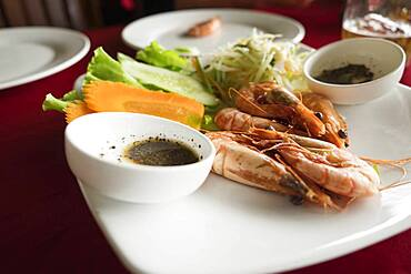Plate of shrimp, carrot and salad on restaurant table