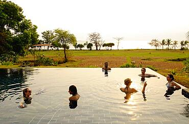 Tourists swimming in infinity pool in remote landscape