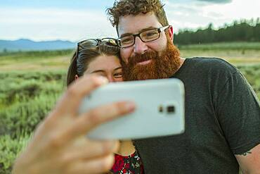 Caucasian couple taking selfie with cell phone in remote field