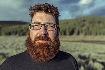 Caucasian man with beard standing in remote field
