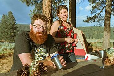 Caucasian couple relaxing at campsite