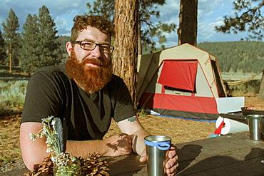 Caucasian man drinking at campsite