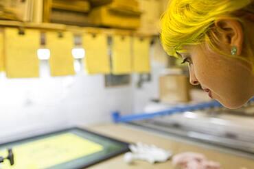 Caucasian artist working in screen print workshop