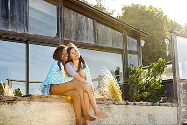 Smiling women hugging in backyard