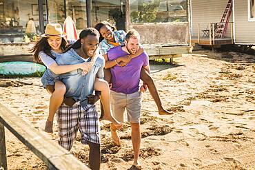 Men carrying girlfriends piggyback in sand