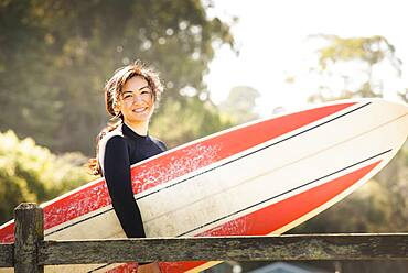 Woman carrying surfboard outdoors
