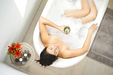 Woman drinking cocktail in bubble bath