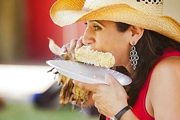 Close up of Hispanic woman eating corn