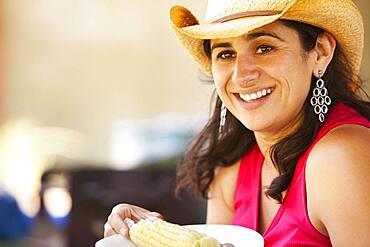Smiling Hispanic woman eating corn